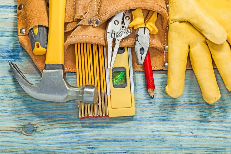 A correia de couro da construção com as ferramentas de funcionamento na placa de madeira mainten fotografia de stock