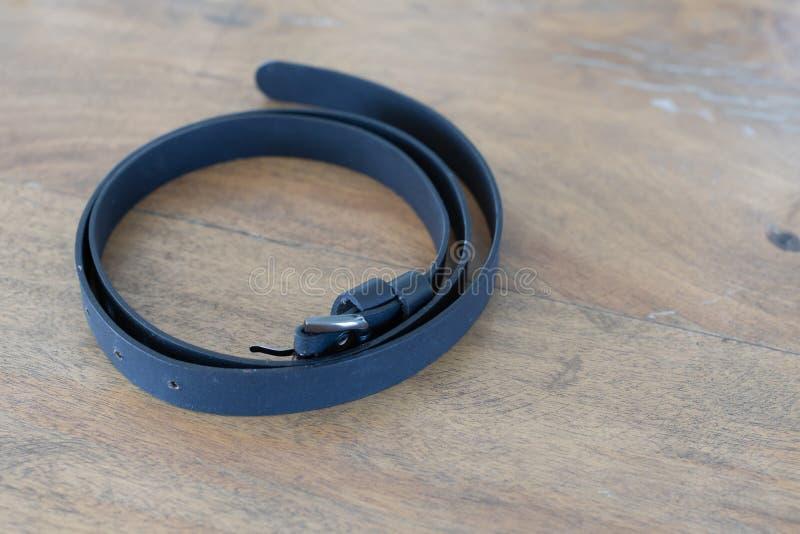 Correia de couro preta na tabela de madeira imagem de stock