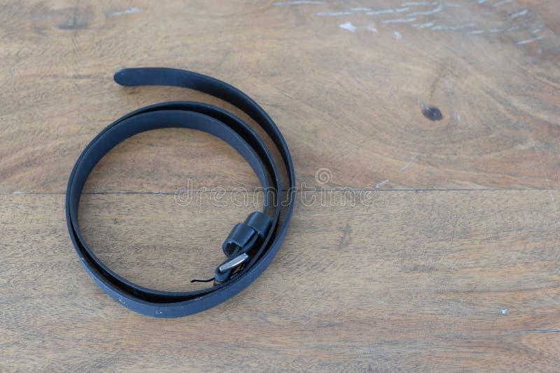 Correia de couro preta na tabela de madeira fotografia de stock