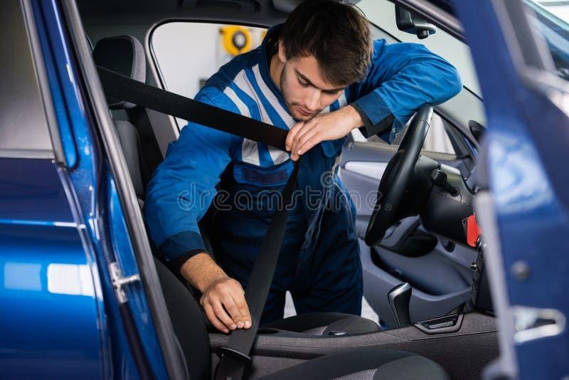 Correia de Examining Car Seat do mecânico imagem de stock