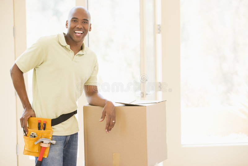 Correia desgastando da ferramenta do homem por caixas na HOME nova imagem de stock