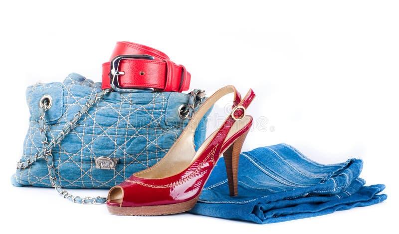 A correia vermelha e as sapatas, calças de brim ensacam e uma saia fotos de stock royalty free