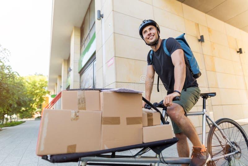 Correio da bicicleta que faz uma entrega imagem de stock