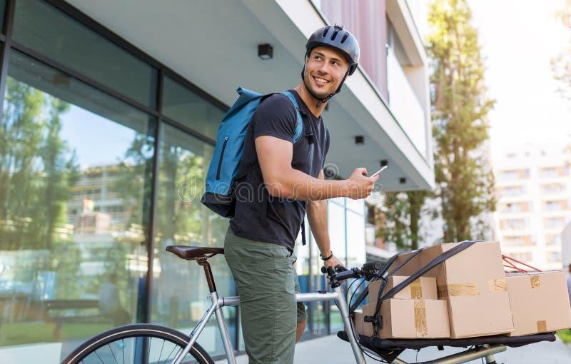 Correio da bicicleta que faz uma entrega fotos de stock