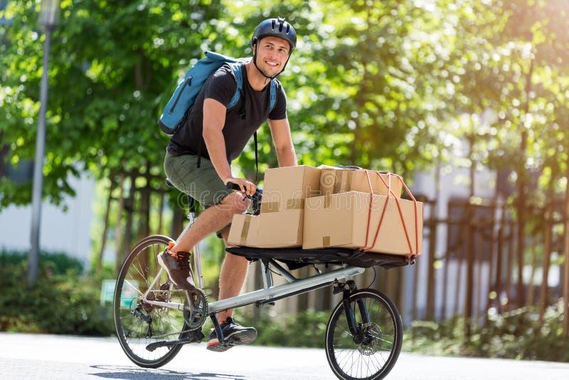 Correio da bicicleta que faz uma entrega fotografia de stock royalty free