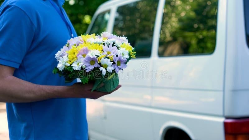 Correio masculino que entrega flores ao cliente, expedição expressa a seu fest da família fotos de stock royalty free