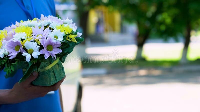 Correio masculino que guarda o ramalhete bonito, a ordem expressa das flores e a entrega imagem de stock
