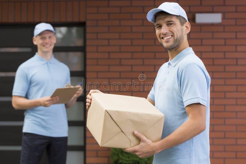 Correio no uniforme azul que guarda um pacote fotografia de stock royalty free
