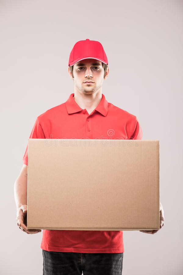 Correio novo feliz alegre do homem de entrega que guarda uma caixa e um sorriso de cartão fotos de stock