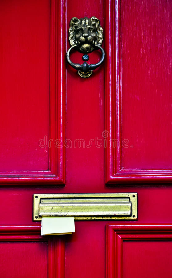 Correio que fura em uma porta de madeira vermelha fotografia de stock royalty free