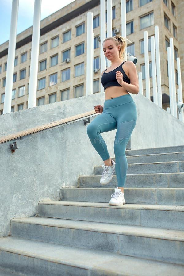 Correndo nella motivazione di sport della città Giovane donna sportiva che corre di sopra sulle scale della citt? immagini stock