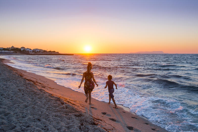 Correndo sul tramonto della spiaggia di estate fotografie stock
