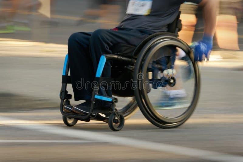Correndo in una sedia a rotelle fotografia stock