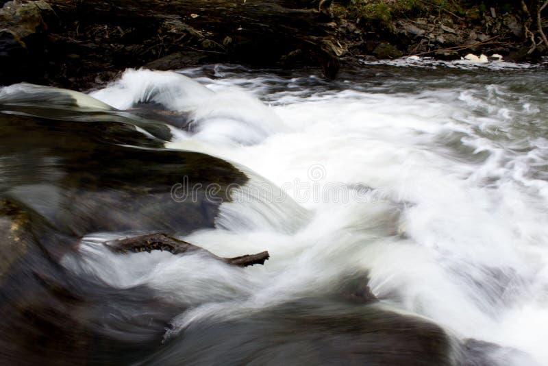Corrente cristallina bianca del fiume che precipita sopra le rocce fotografia stock