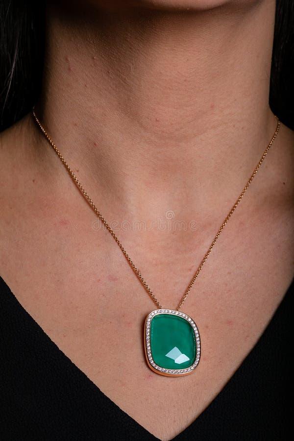 A corrente das mulheres do ouro com um pendente, uma pedra verde no meio e uma franja dos diamantes que penduram em torno de seu  imagem de stock royalty free