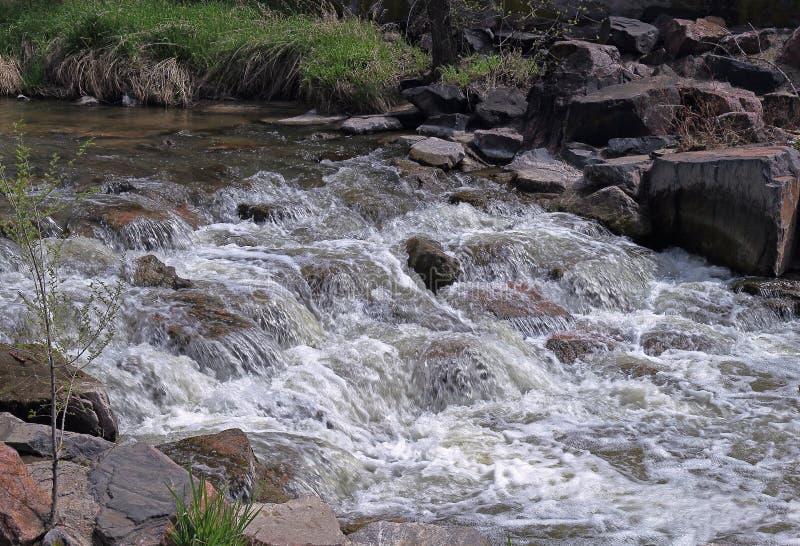 Corrente dell'acqua che investe le rocce Cherry Creek a Denver immagini stock libere da diritti