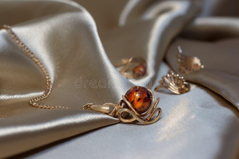 Corrente do ouro do close up com o pendente do ouro e do âmbar Báltico autêntico na luz - atlas marrom foto de stock royalty free