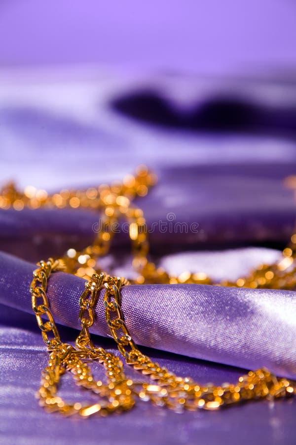 Corrente dourada na seda brilhante fotografia de stock royalty free