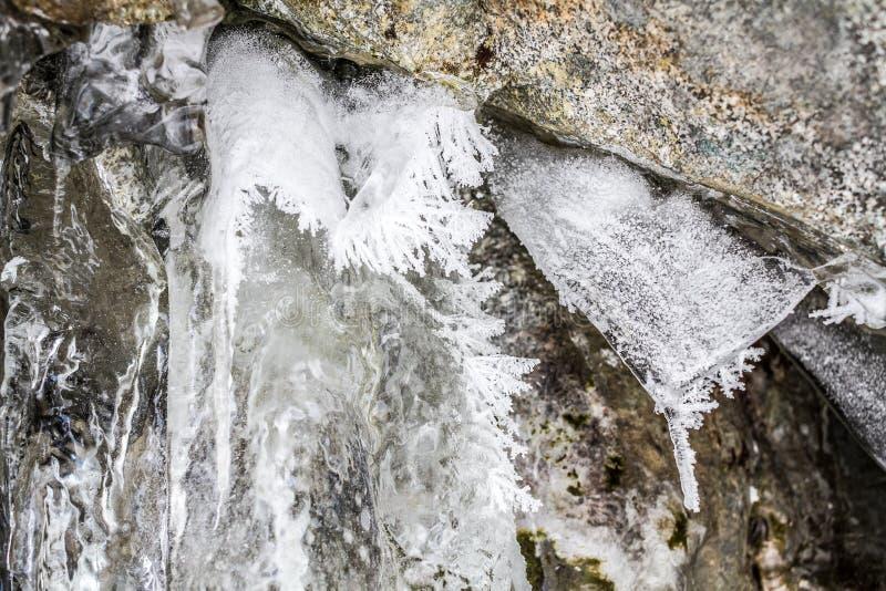 Corrente ghiacciata fra le rocce fotografia stock libera da diritti