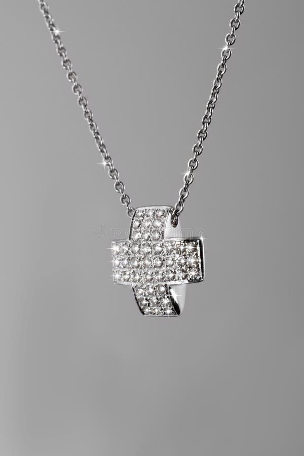 Corrente preciosa da platina com os diamantes transversais no fundo cinzento fotografia de stock royalty free