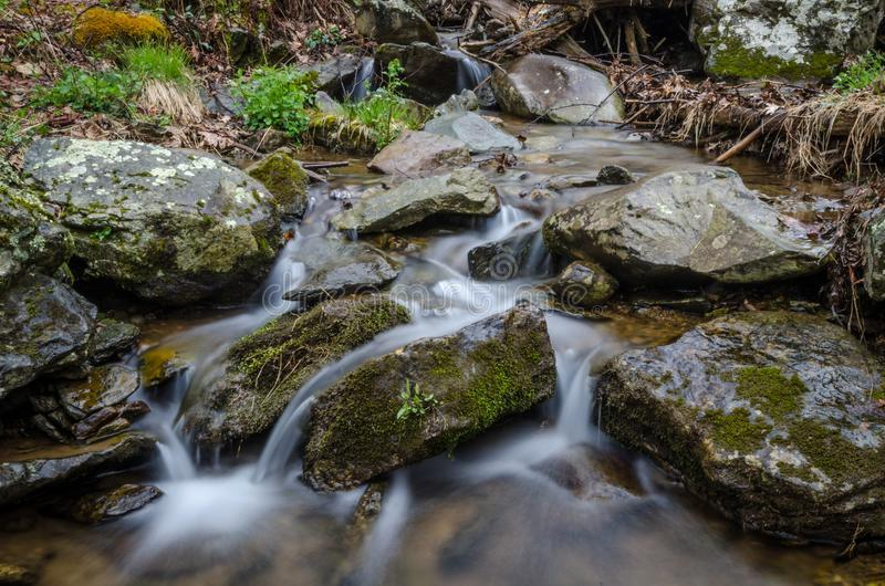 Corrente serena calma che scorre intorno alle grandi rocce immagini stock