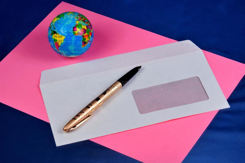 Correo del papel de sobre, papel rosado, pluma para escribir, globo del mundo Sobre de envío de papel con una ventana para las et foto de archivo libre de regalías