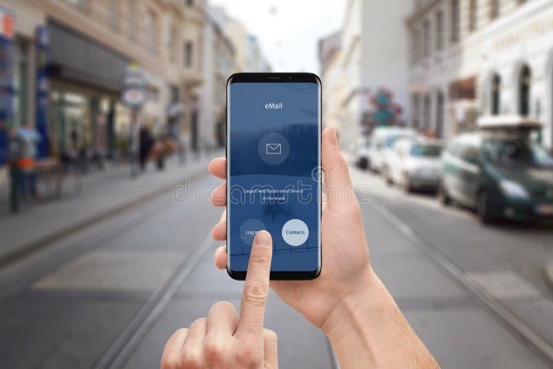 Correo electrónico app del uso del hombre en el teléfono móvil Teléfono elegante moderno con los bordes redondos y diseño de inte imágenes de archivo libres de regalías