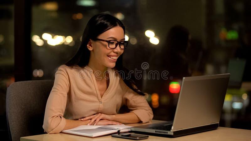 Correo electrónico femenino sonriente del ordenador portátil de la lectura del freelancer, educación en línea, lección video fotografía de archivo libre de regalías