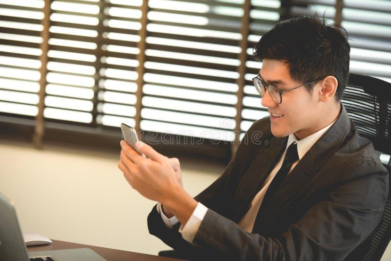 Correo electrónico joven de la lectura del hombre de negocios en el teléfono elegante foto de archivo libre de regalías