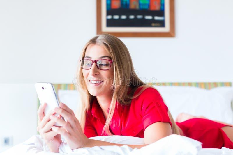 Correos de la lectura de la mujer en smartphone fotos de archivo libres de regalías