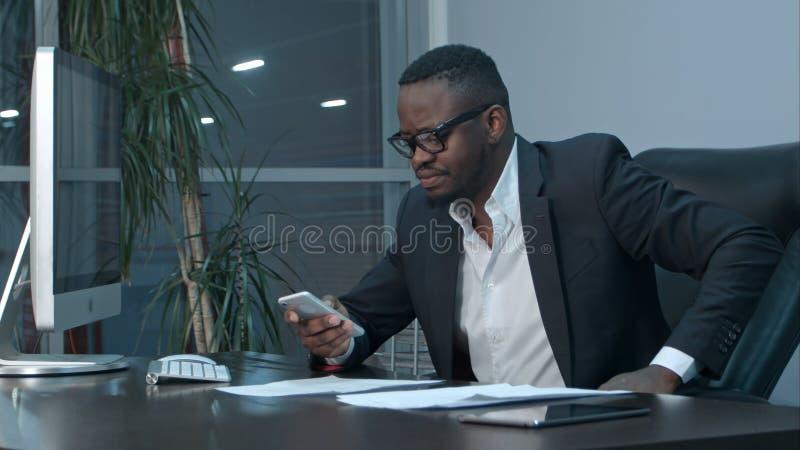 Correos electrónicos afroamericanos de la lectura del hombre de negocios en su smartphone y respuestas que mandan un SMS fotos de archivo