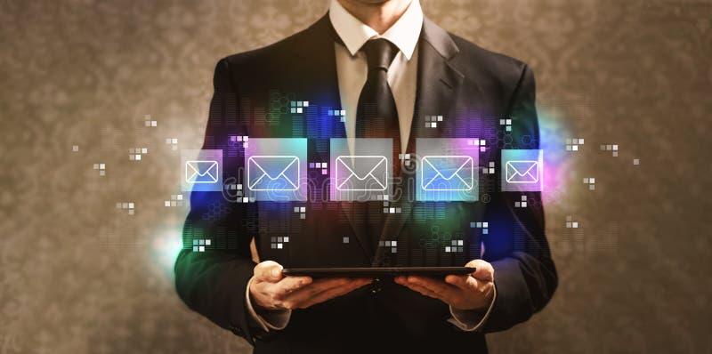 Correos electrónicos con el hombre de negocios que sostiene una tableta foto de archivo