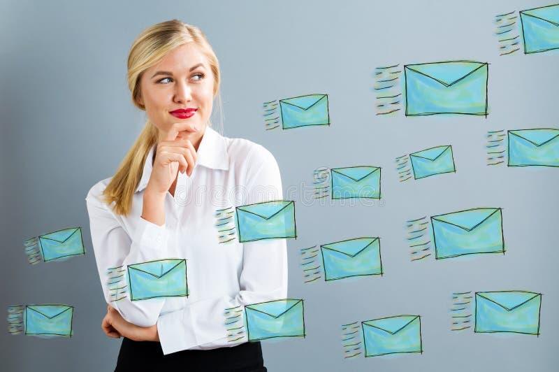 Correos electrónicos con la mujer de negocios joven foto de archivo