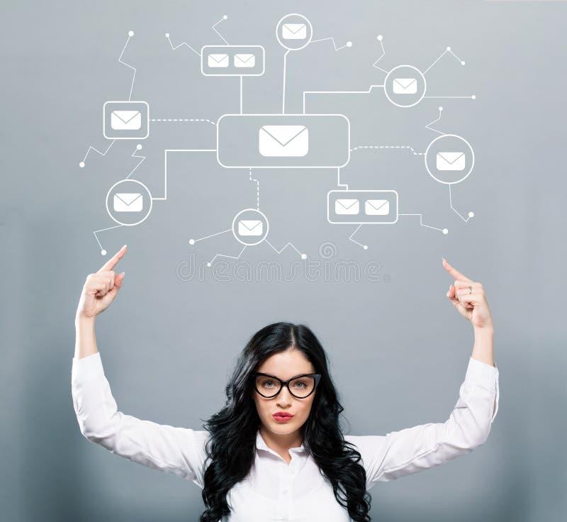 Correos electrónicos con la mujer de negocios que señala hacia arriba fotografía de archivo