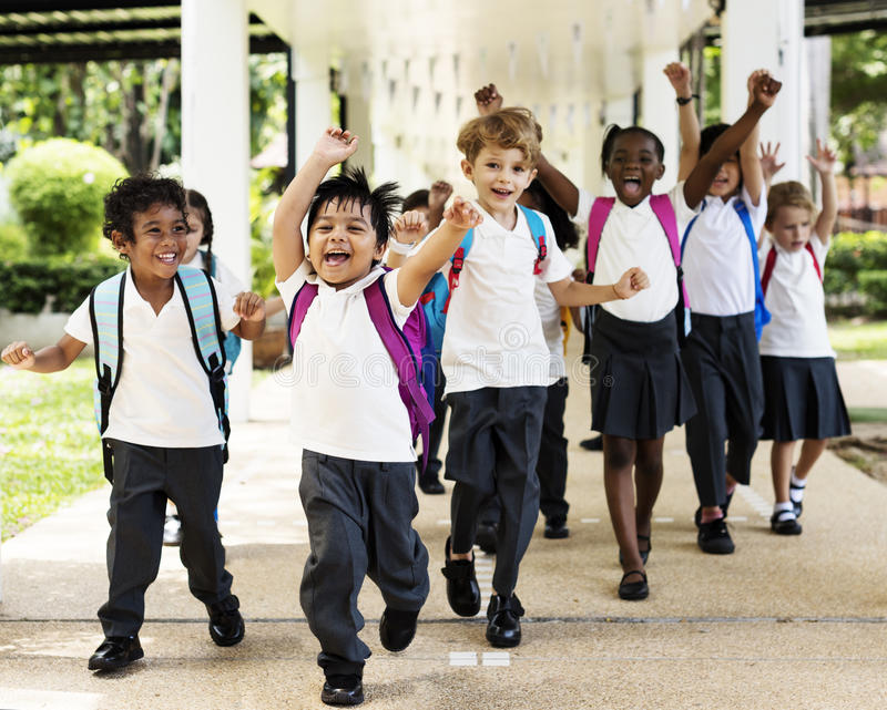 Correre degli studenti di asilo allegro dopo classe immagini stock