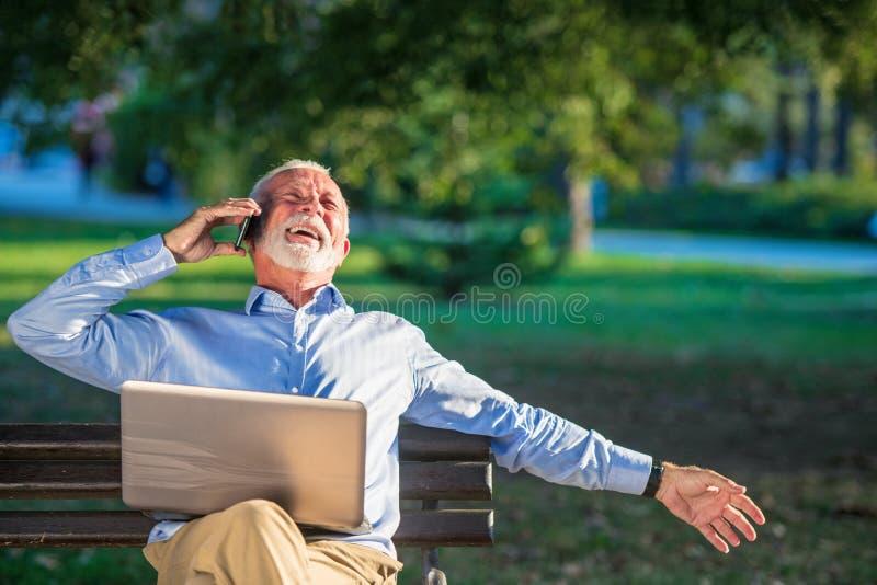Correspondencia de negocio Hombre de negocios maduro enfocado usando el ordenador portátil mientras que se sienta en parque fotografía de archivo