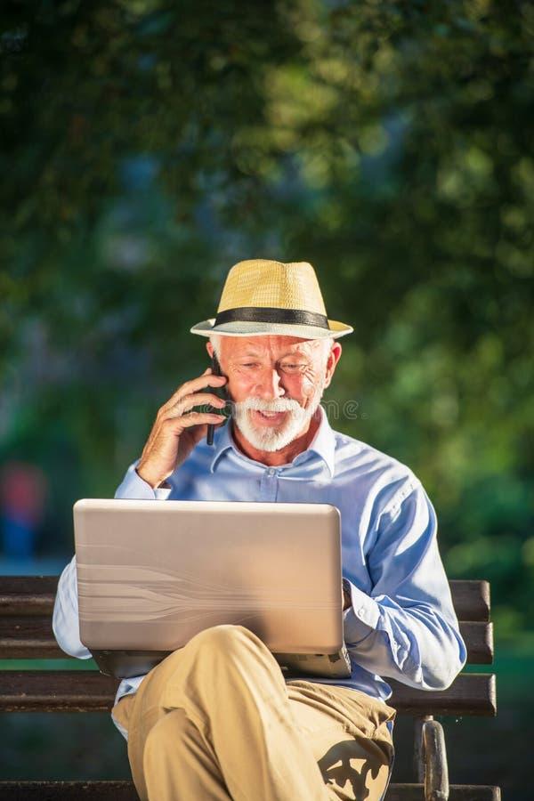Correspondencia de negocio Hombre de negocios maduro enfocado usando el ordenador portátil mientras que se sienta en parque fotos de archivo libres de regalías
