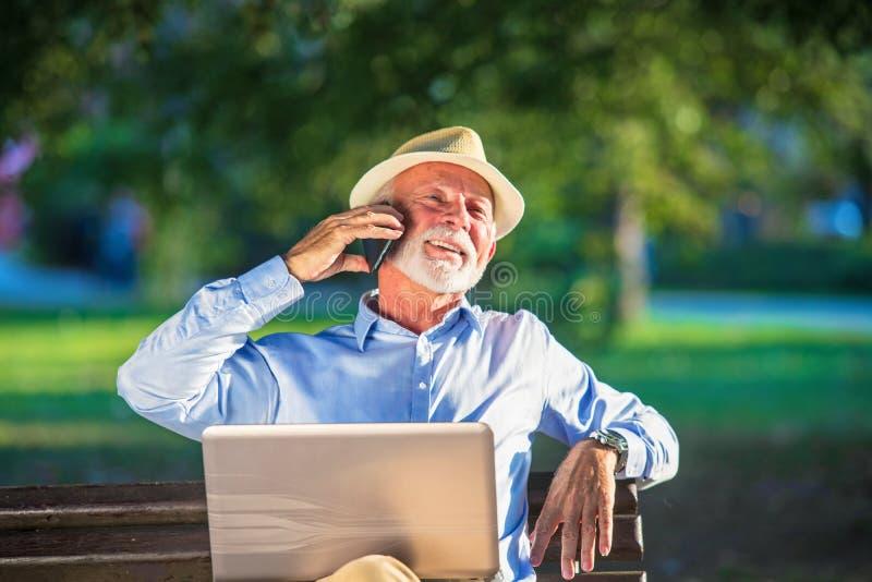 Correspondencia de negocio Hombre de negocios maduro enfocado usando el ordenador portátil mientras que se sienta en parque fotografía de archivo libre de regalías