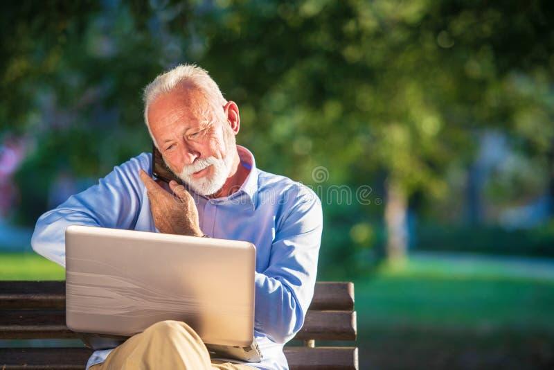 Correspondencia de negocio Hombre de negocios maduro enfocado usando el ordenador portátil mientras que se sienta en parque foto de archivo