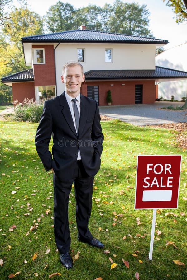 Corretor da propriedade ereto fora da casa imagem de stock