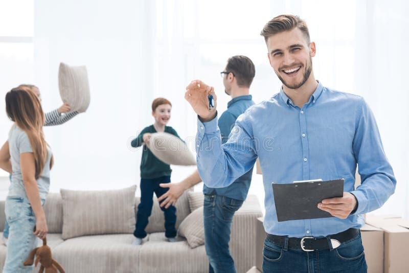 Corretor de imóveis bem sucedido que mostra as chaves a um apartamento novo imagens de stock