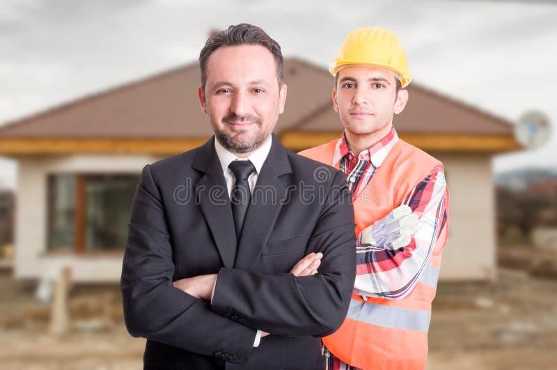 Corretor de imóveis e construtor consideráveis atrás dele imagens de stock royalty free
