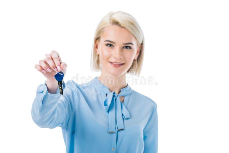 corretor de imóveis fêmea de sorriso que guarda chave da casa nova, imagem de stock