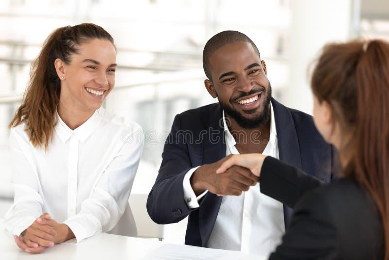 Corretor de imóveis misturado feliz do segurador do aperto de mão dos clientes dos pares da afiliação étnica que faz o negócio fotografia de stock royalty free