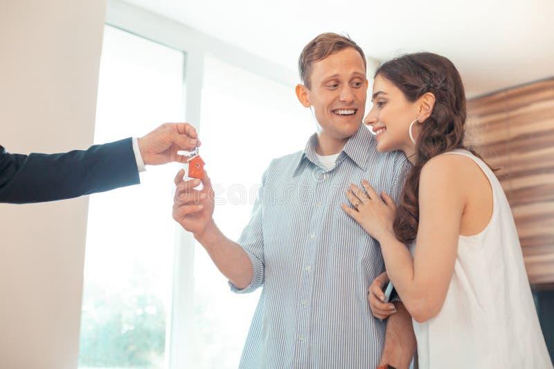 Corretor de imóveis que dá as chaves para acoplar-se após ter comprado a casa imagem de stock