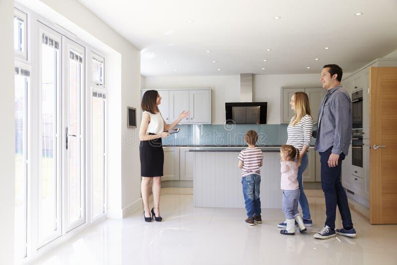 Corretor de imóveis que mostra a família nova em torno da propriedade para a venda fotografia de stock royalty free