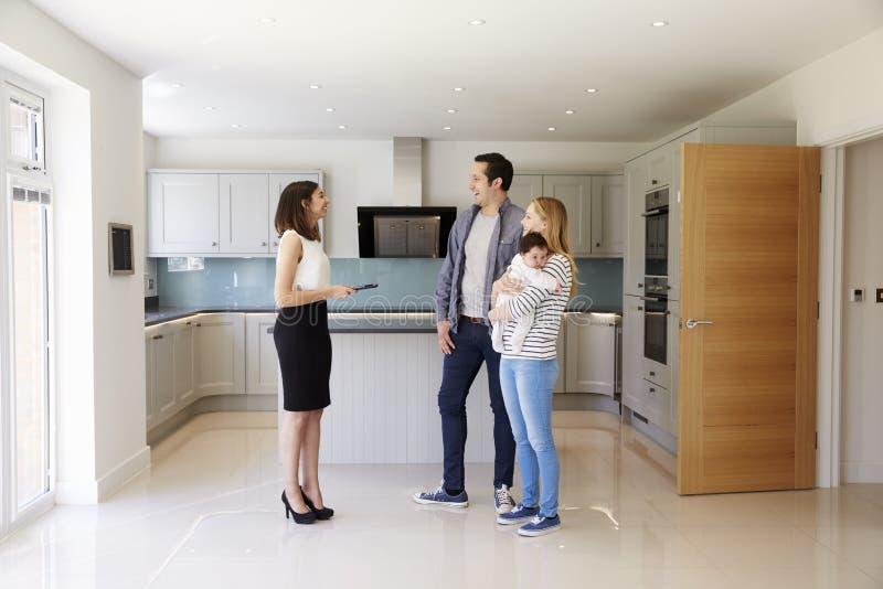 Corretor de imóveis que mostra a família nova em torno da propriedade para a venda imagens de stock