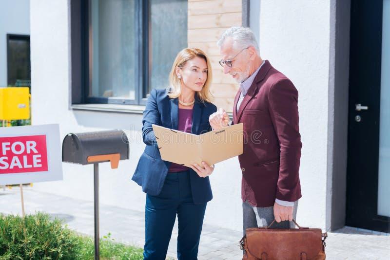 Corretor imobiliário profissional que fornece a informação necessária o cliente imagens de stock royalty free