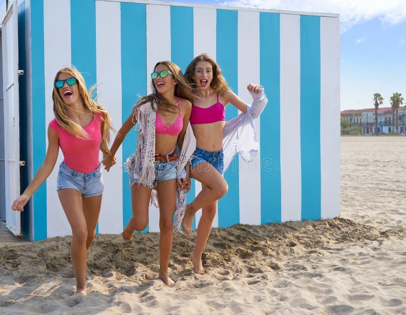 Corrida adolescente das meninas dos melhores amigos feliz na praia foto de stock
