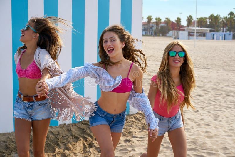 Corrida adolescente das meninas dos melhores amigos feliz na praia imagens de stock
